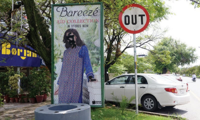 Photographs of models on these billboards in an Islamabad market have been defaced. — Photos by Ishaque Chaudhry
