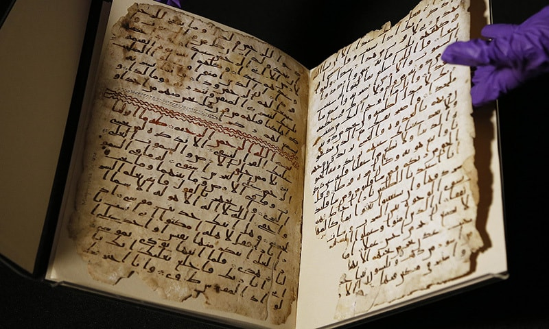 A university assistant shows fragments of an old Quran at the University in Birmingham, in Birmingham central England Wednesday, July 22, 2015. —AP