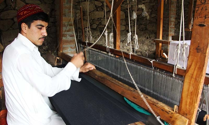 An artisan is weaving a woolen shawl on his handloom. — Photo by author