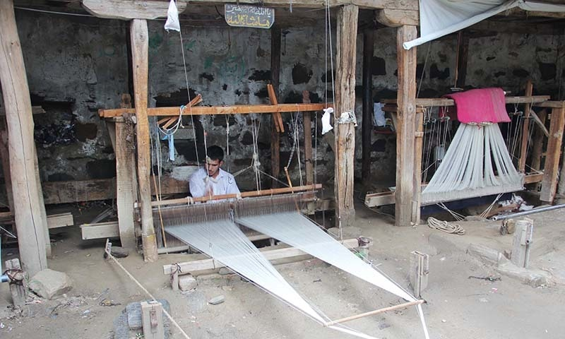 An artisan is weaving woolen shawl on his hand loom. — Photo by author