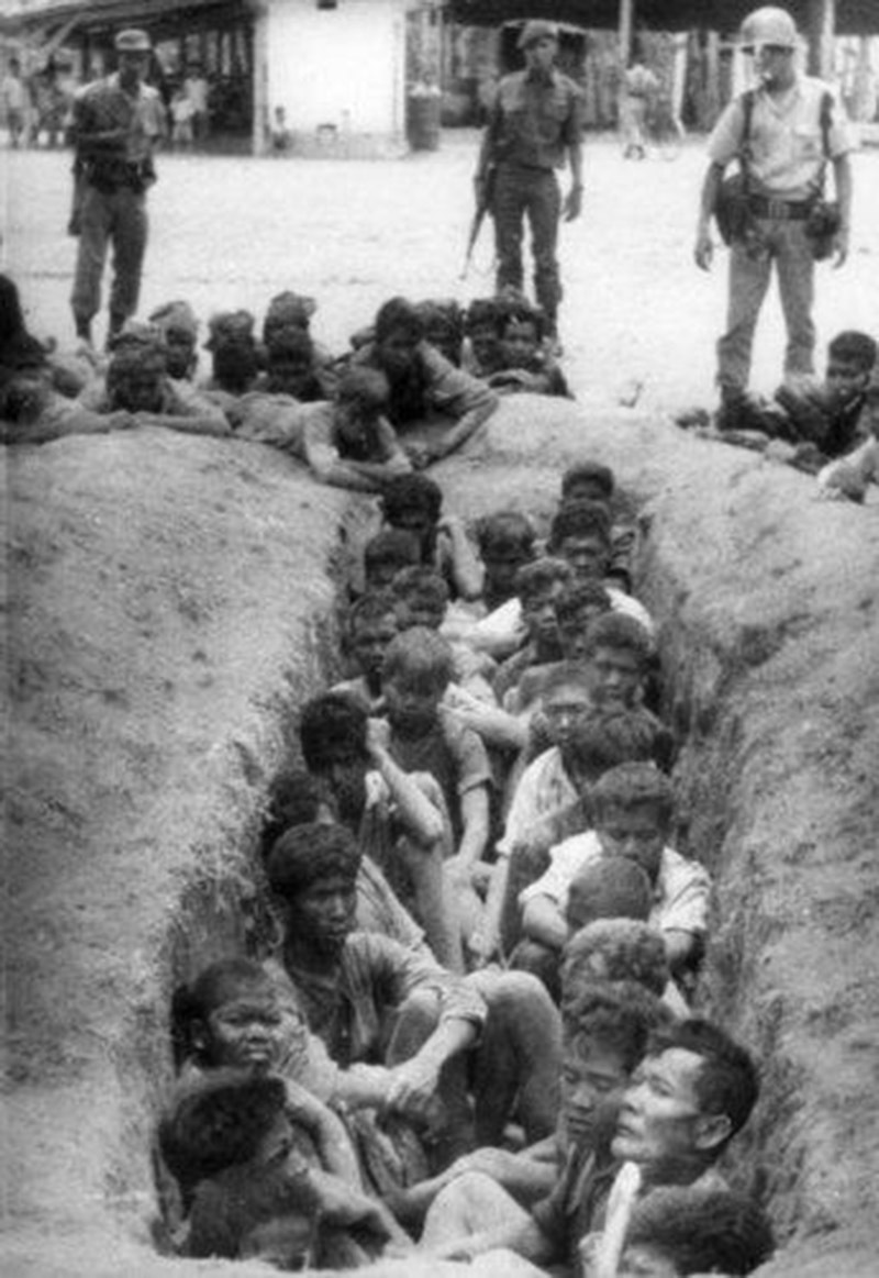 Soldiers guard a ditch full of leftist Indonesian activists. They were all shot (1965).