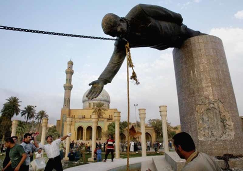 Protesters pull down Saddam Hussein's statue in Baghdad (2003).