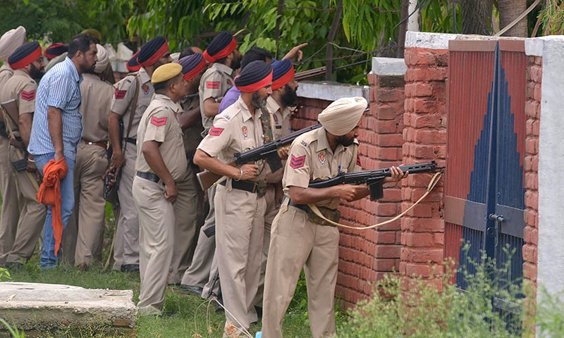 Indian Punjab police personnel take position during an encounter with armed attackers at the police station. ─ AFP