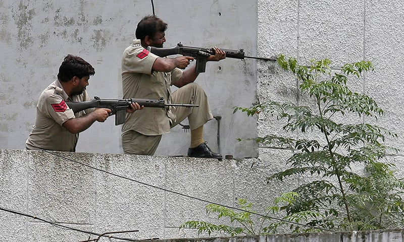 Policemen take their positions next to a police station during a gunfight at Dinanagar town in Gurdaspur district of Punjab, India. —Reuters