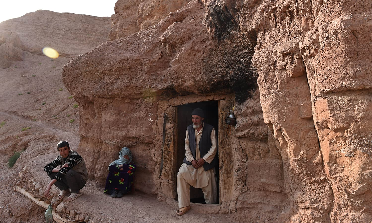 In this photograph taken on June 19, 2015, a Hazara Afghan family look on in front of their cave in the old city of Bamiyan, some 200 kilometres (124 miles) northwest of Kabul. ─ AFP