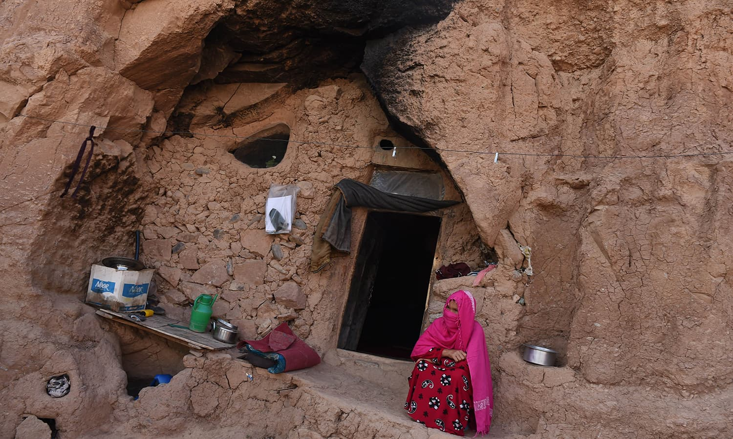 In this photograph taken on June 19, 2015, a Hazara Afghan woman sits by the entrance to her cave in the old city of Bamiyan, some 200 kilometres (124 miles) northwest of Kabul. ─ AFP