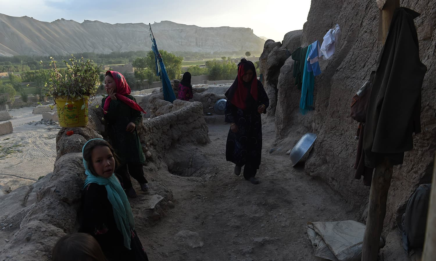 In this photograph taken on June 19, 2015, a Hazara Afghan family stands by the entrance to their cave in the old city of Bamiyan, some 200 kilometres (124 miles) northwest of Kabul. ─ AFP