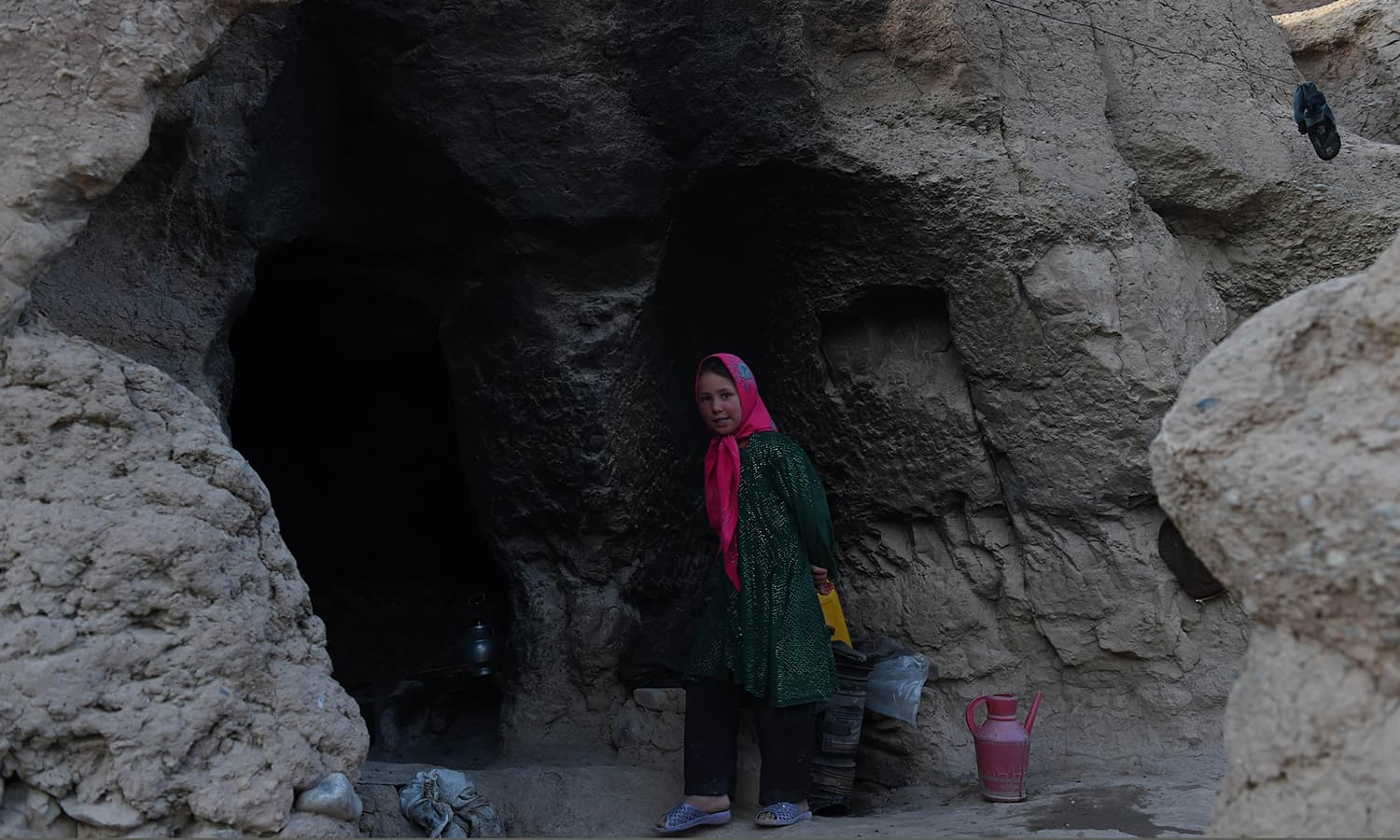 In this photograph taken on June 19, 2015, a Hazara Afghan girl looks on as her mother cooks inside their cave in the old city of Bamiyan, some 200 kilometres (124 miles) northwest of Kabul. ─ AFP