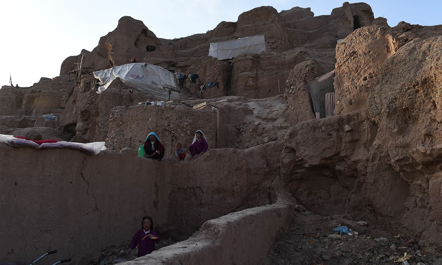 In this photograph taken on June 19, 2015, a Hazara Afghan women wash dishes in front of their caves in the old city of Bamiyan, some 200 kilometres (124 miles) northwest of Kabul. ─ AFP