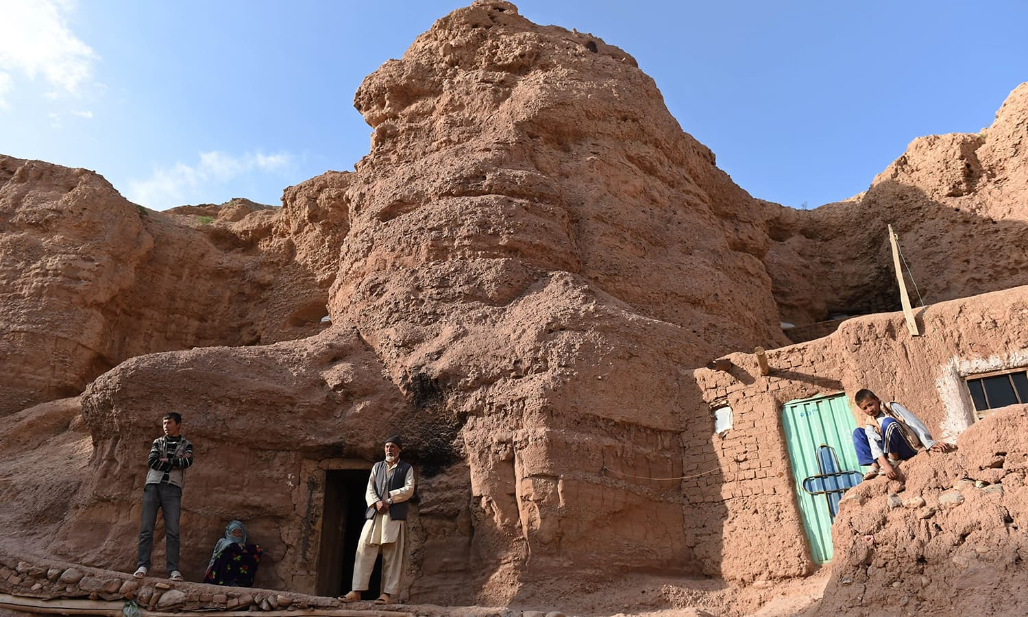 In this photograph taken on June 19, 2015, a Hazara Afghan family stands in front of their cave in the old city of Bamiyan, some 200 kilometres (124 miles) northwest of Kabul. ─ AFP