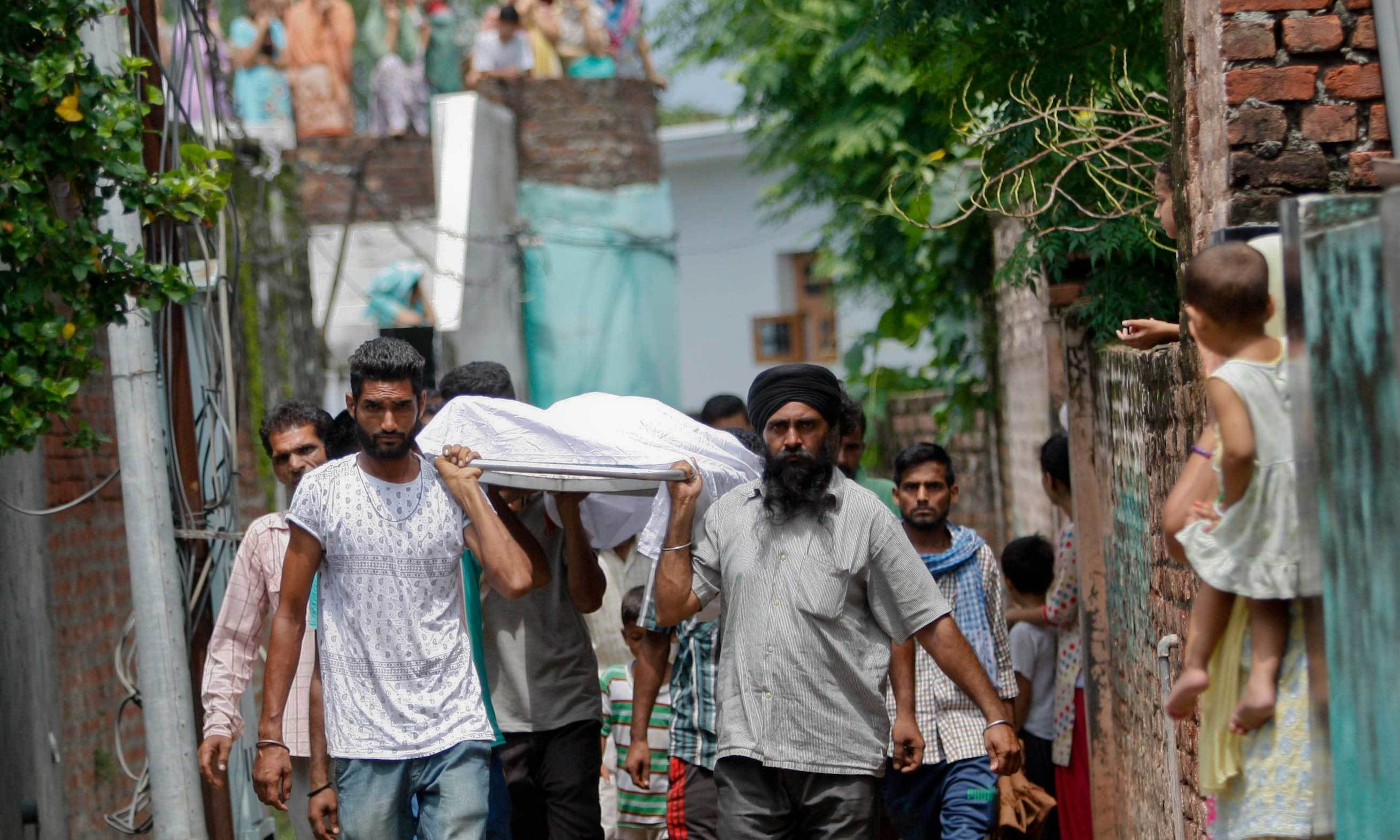 Indian people carry the body of Des Raj, who was killed in a rebel attack at his village in Dinanagar, India, Tuesday, July 28, 2015. – AP