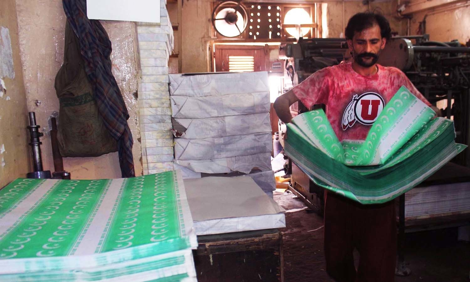 Labourer working at a printing press busy in printing national  flags bunting on arrival of Pakistan Independence Day ahead on August 14, at Pakistan Chowk  in Karachi. ─ PPI