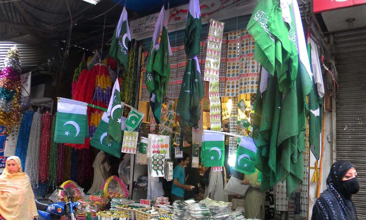 A whole sale dealer in Rawalpindi arranging the Independence Day related commodities at Urdu Bazaar as the nation starts preparations to celebrate the Independence Day of Pakistan in befitting manners. ─ INP