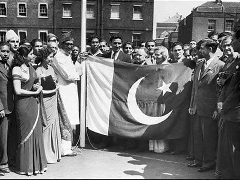A group of people raising the Pakistani flag one day after Pakistan came into being on August 14, 1947.
