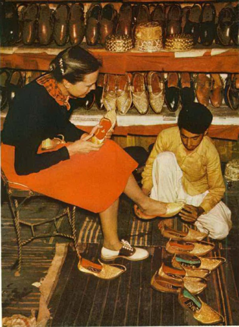 A British tourist trying out traditional shoes at a shop in Swat (NWFP) in 1952.