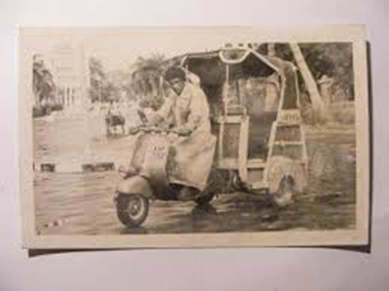 A 'scooter-rickshaw' riding across a road in Karachi in 1960.