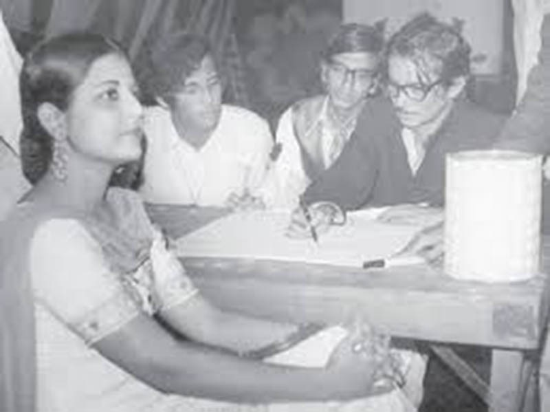 Pakistani painter and sculptor, Sadequain, drawing a portrait of a fan during an art's festival in Lahore (1972).
