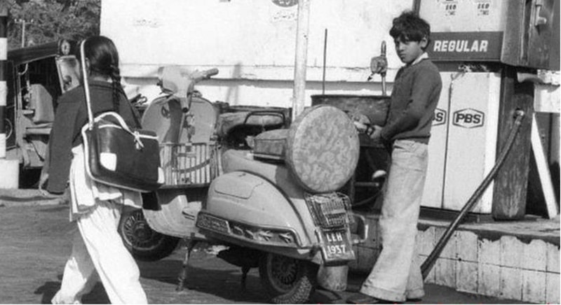 A young boy fills the tank of his dad's motorbike as a girl walks towards her school in Lahore (1974).