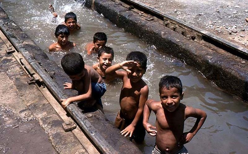 Young children beat the heat by taking a dip in the bogy washing area of Peshawar Railway Station in 1980.