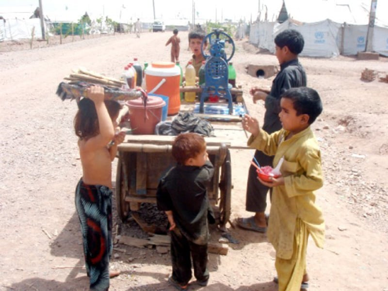 Kids enjoy a round of 'gola gunda' (snow ice-cream) at Karachi's low-income Orangi area in 1992.