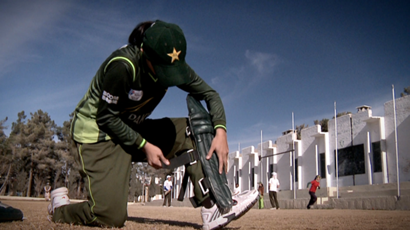 A member of the Pakistan women's cricket team pads up in Lahore (2010).