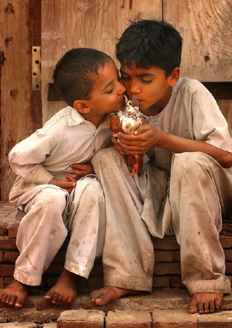 Two kids kiss a pigeon in a working class area of Lahore (2011).