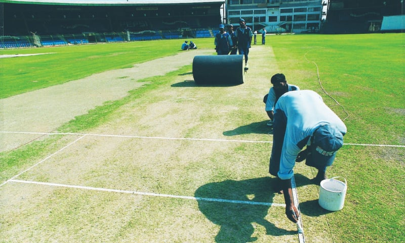 Curators at the National Stadium Karachi put finishing touches to a strip