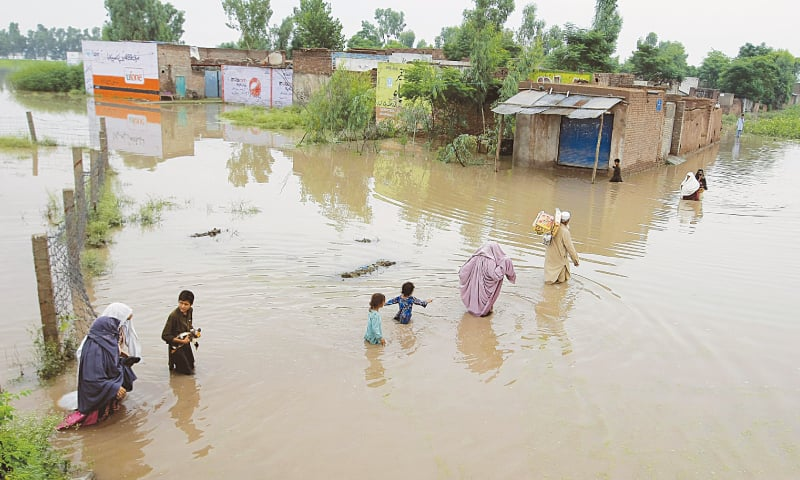 NOWSHERA: People wade through floodwaters in a village near here on Sunday after torrential rainfall.—AP