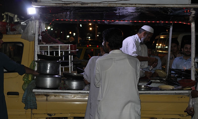 Shaukat Khan, preparing dinner for his customers in his mobile restaurant. — Photo by author