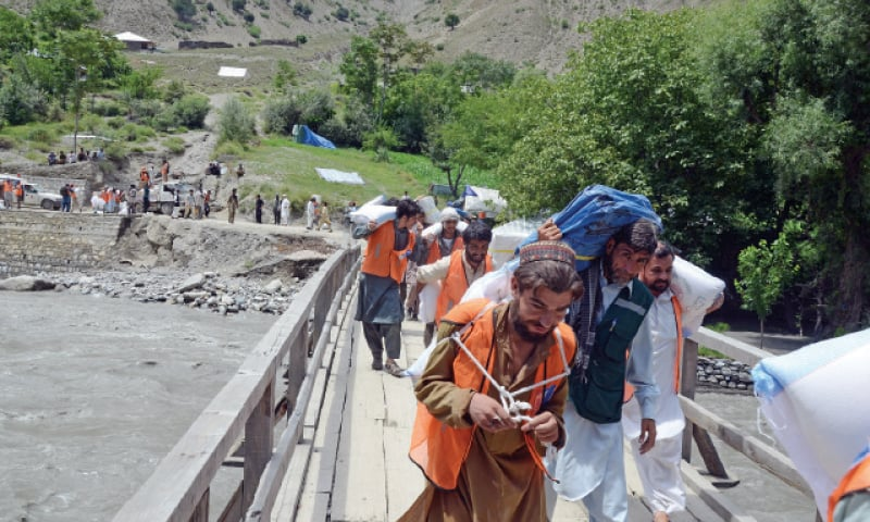 Volunteers carrying relief goods cross a suspension bridge restored by the C&W department to link flood-hit Shoghor village with Chitral. — Photo by Zahiruddin