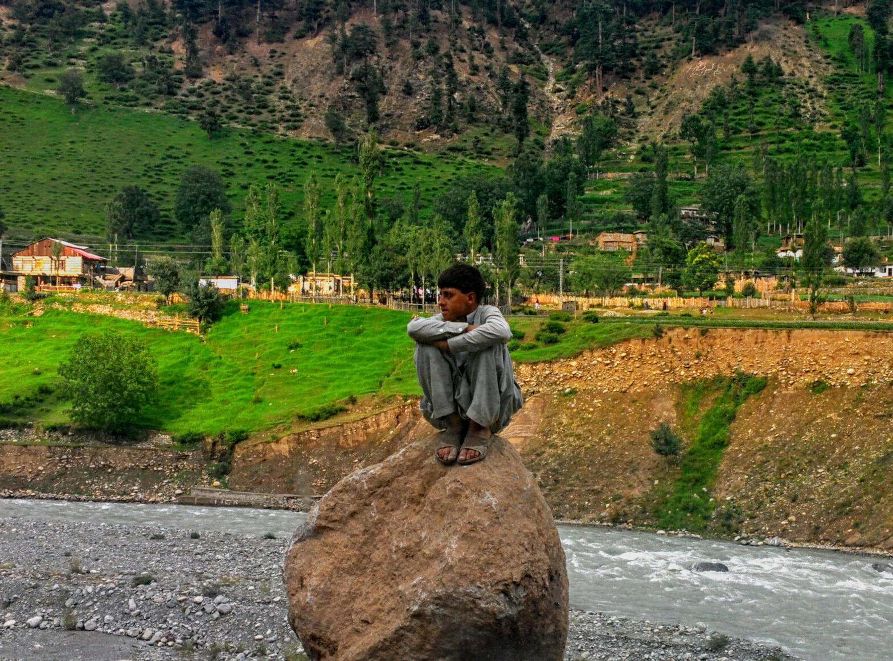 A boy sitting on a rock by his lonesome.