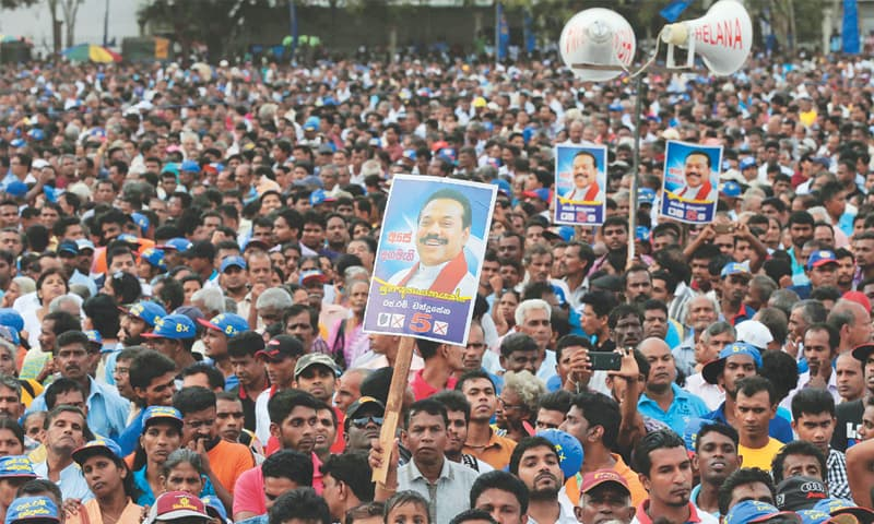 SUPPORTERS listen to Sri Lanka's former president and parliamentary candidate Mahinda Rajapaksa at an election campaign rally in Anuradhapura on July 17.—AP
