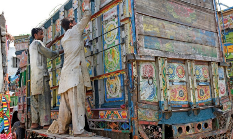 Workers put fresh coats of paint on the faded embellishments on this old truck. — Photos by Tanveer Shahzad