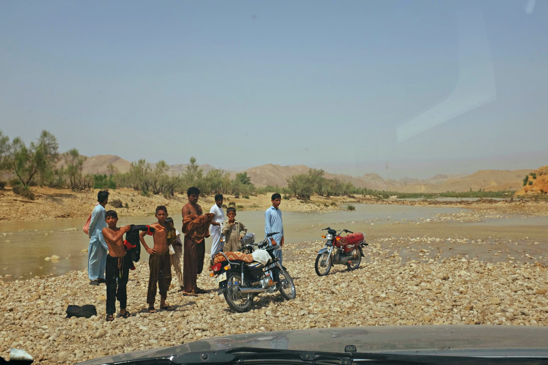 People of nearby villages gather at a stream to take a dip.