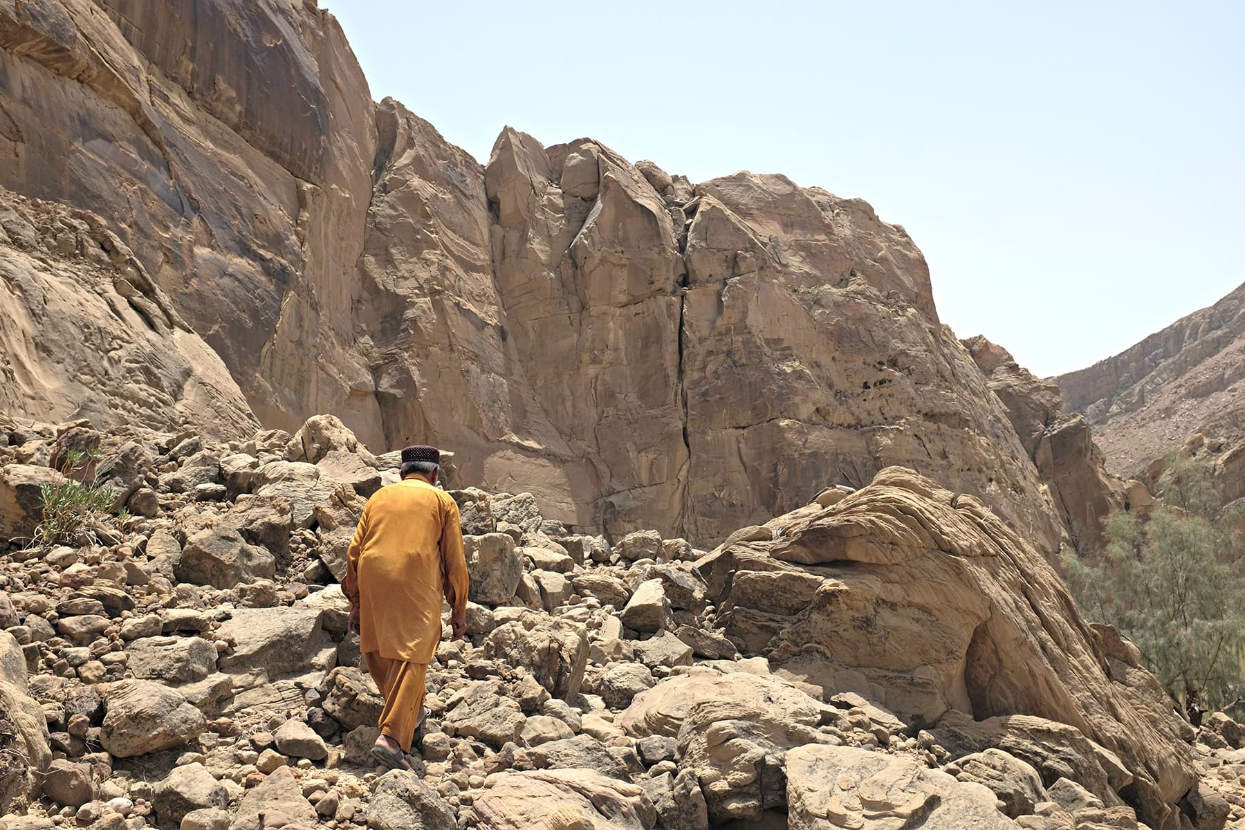 Miskeen walks us to climb other rocks where prominent chiti can be found.
