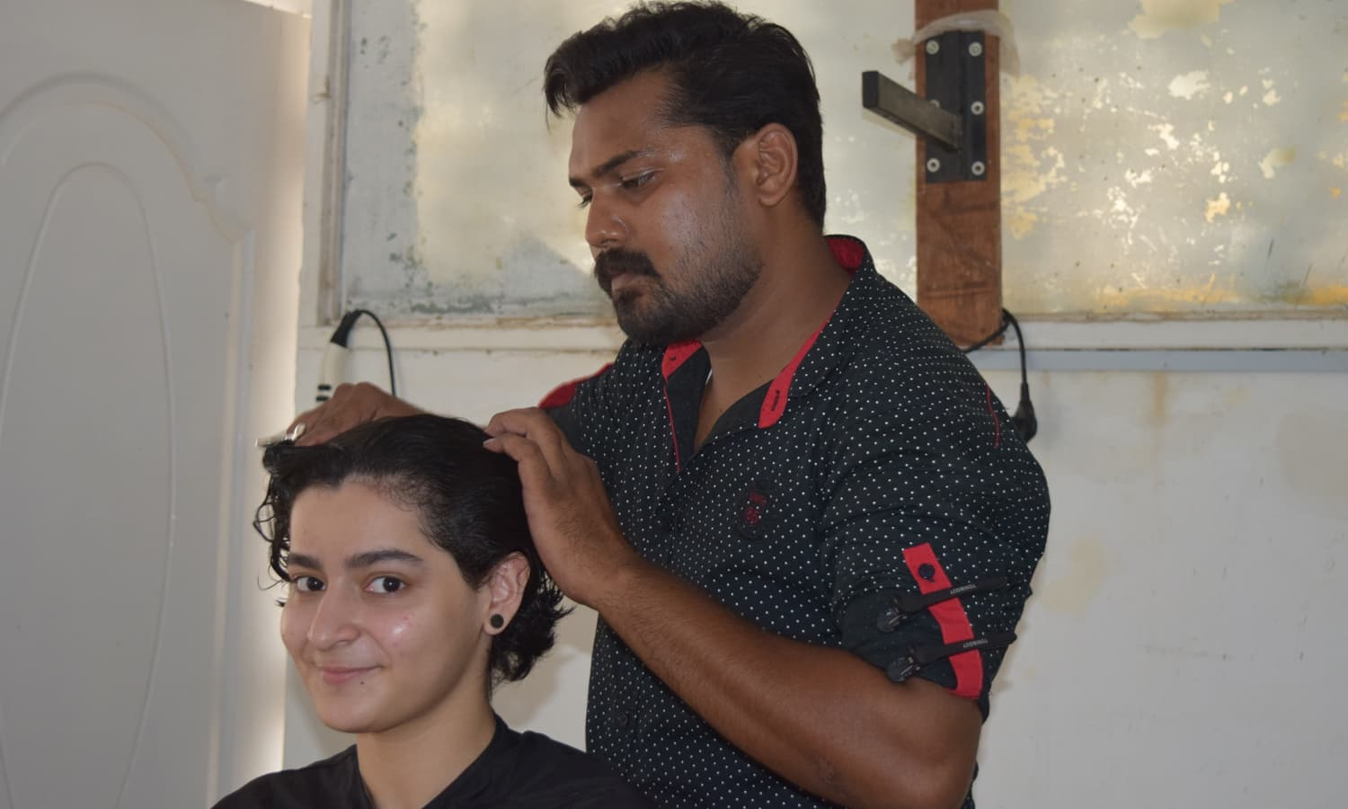 Maria smiles as Inder, the stylist gets done with the haircut. — Photo by Yumna Rafi