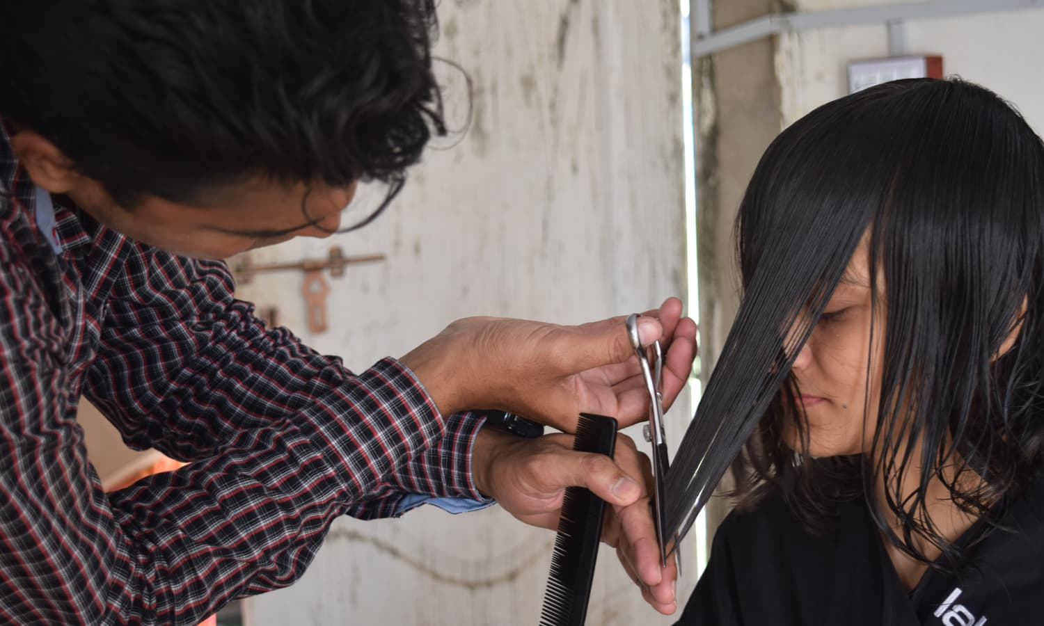 Shahid eyes precision as he cuts one participant's hair. — Photo by Yumna Rafi