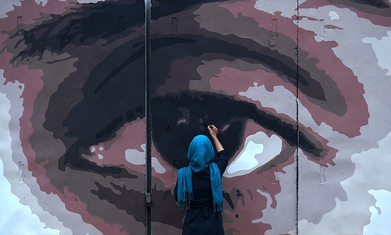 An Afghan artist paints the design of the eyes of a woman on a barrier wall at the presidential palace in Kabul. ─ AFP