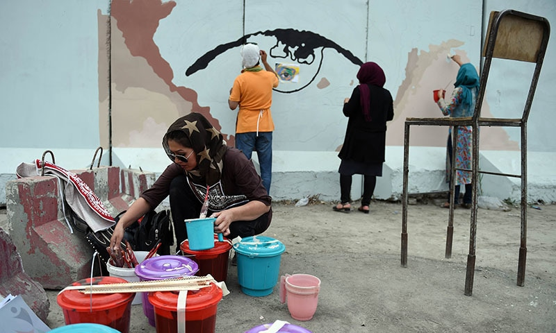 Afghan artists and volunteers paint the design of the eyes of a woman on a barrier wall at the presidential palace in Kabul. ─ AFP