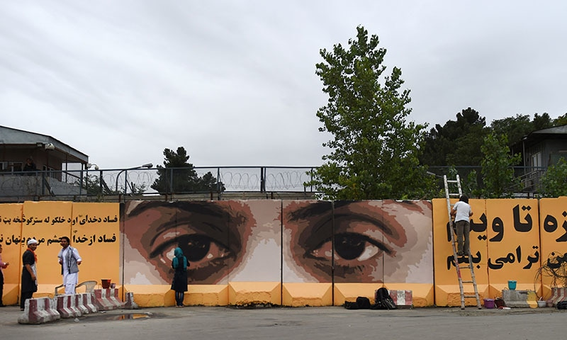 Afghan artists paint the inscription 'corruption is not hidden from God and people's eyes' alongside an image of the eyes of a woman on a barrier wall at the presidential palace in Kabul. ─ AFP