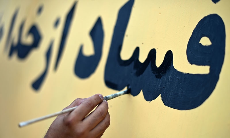 An Afghan artist paints the inscription 'corruption is not hidden from God and people's eyes' on a barrier wall at the presidential palace in Kabul. ─ AFP