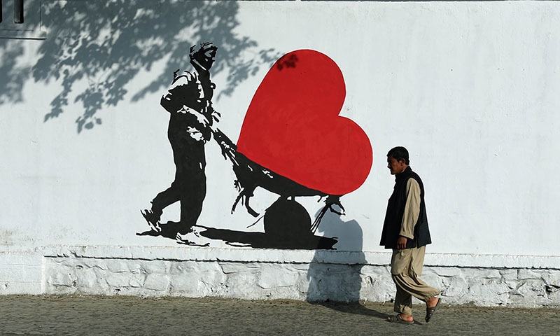 An Afghan pedestrian walks past a painting on a wall showing a man pushing his wheelbarrow with a heart aimed to combat corruption in Kabul. ─ AFP
