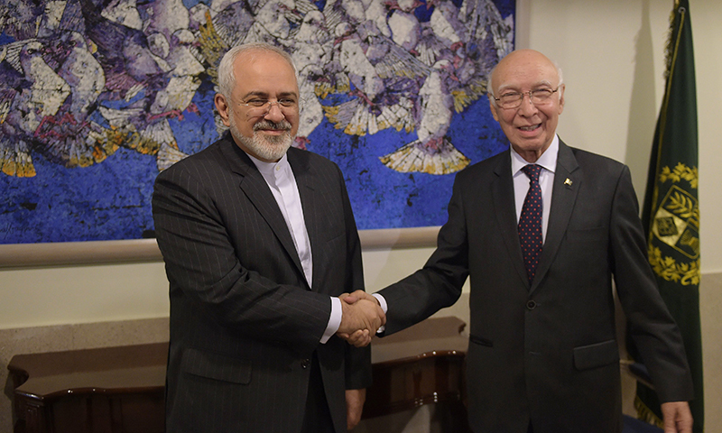 Sartaj Aziz shakes hands with Iranian Foreign Minister Javad Zarif at the Foreign Ministry. —AP