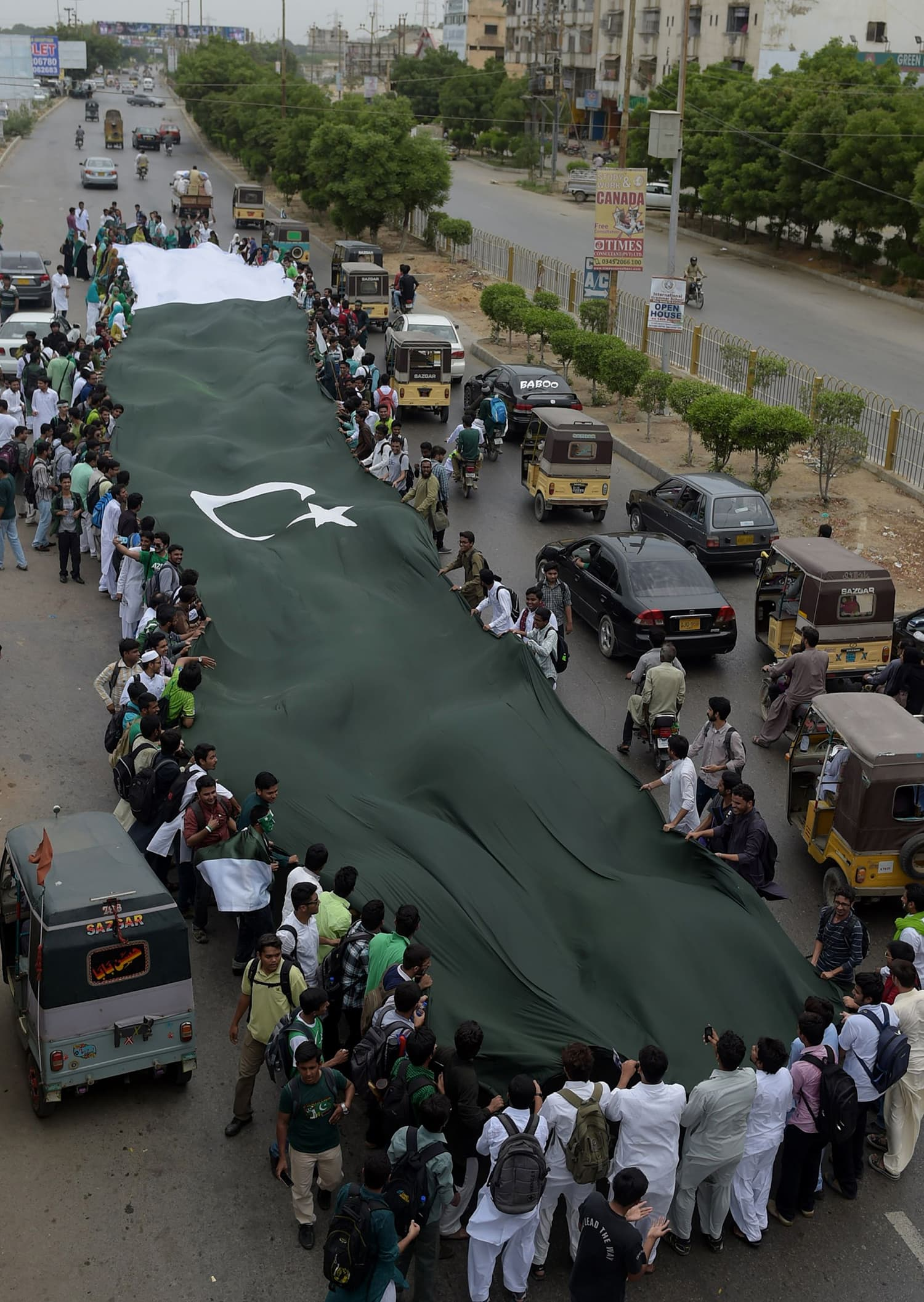 Students carry a national flag as they march on a street ahead of the country's forthcoming Independence Day celebrations in Karachi. — AFP