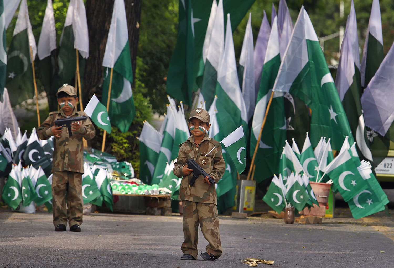 Children hold toy guns and dress as army soldiers to attract customers into their father's stall selling national flags ahead of country's 69th Independence Day in Islamabad. — AP