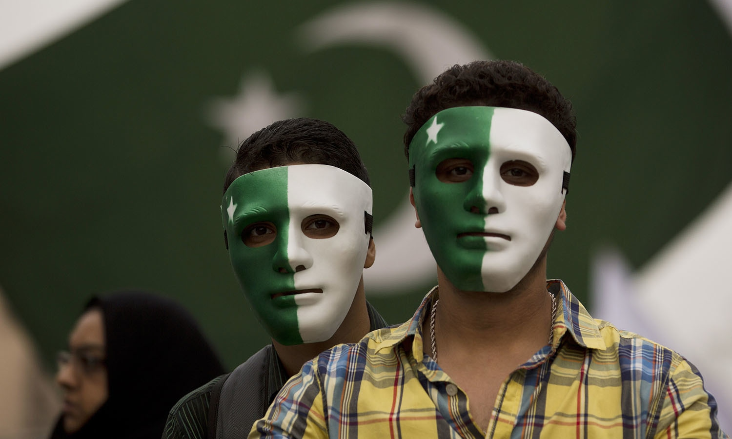 Youngsters wear masks painted in the design of the national flag. — AP