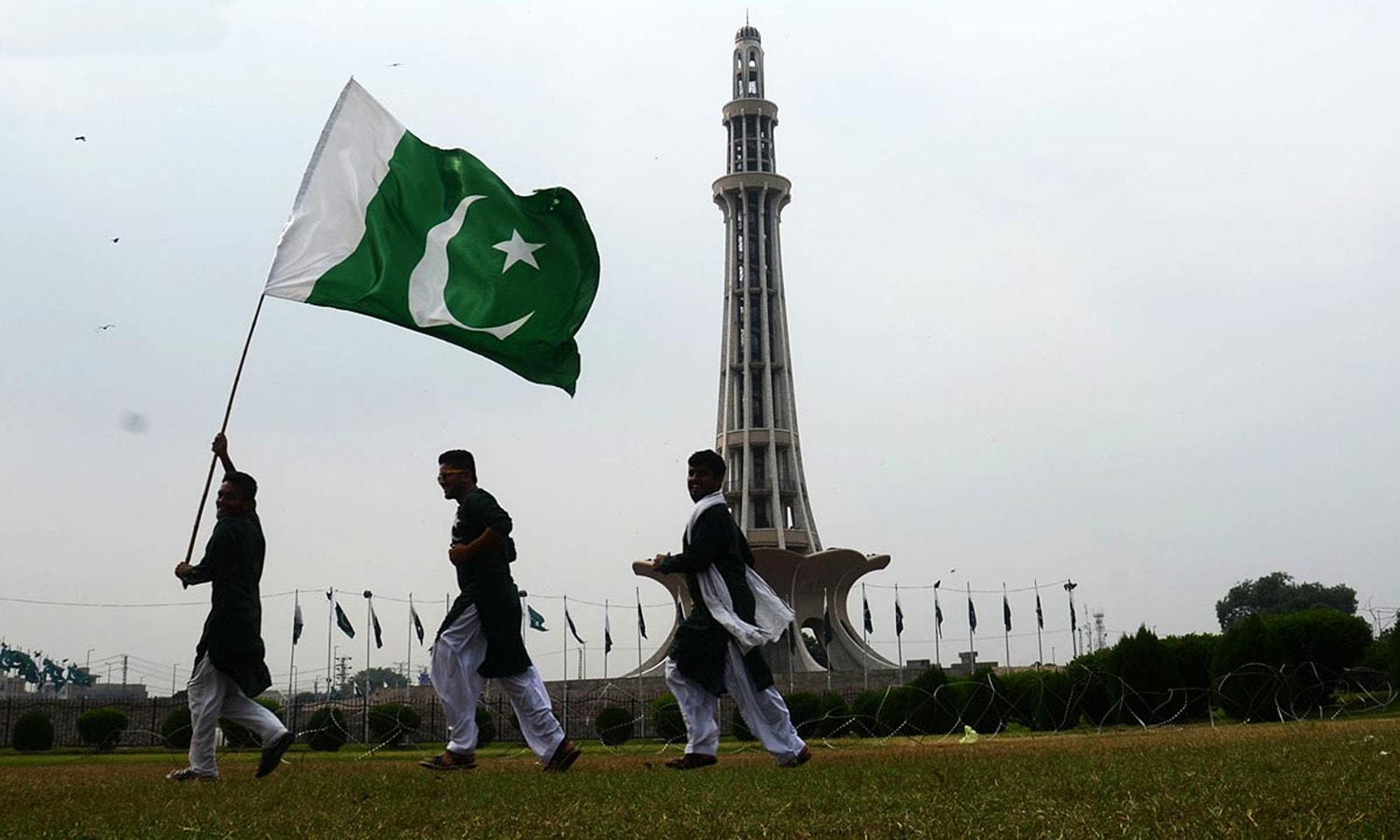 People holding national flag at Minar e Pakistan in connection to Independence Day, in Lahore.— Online