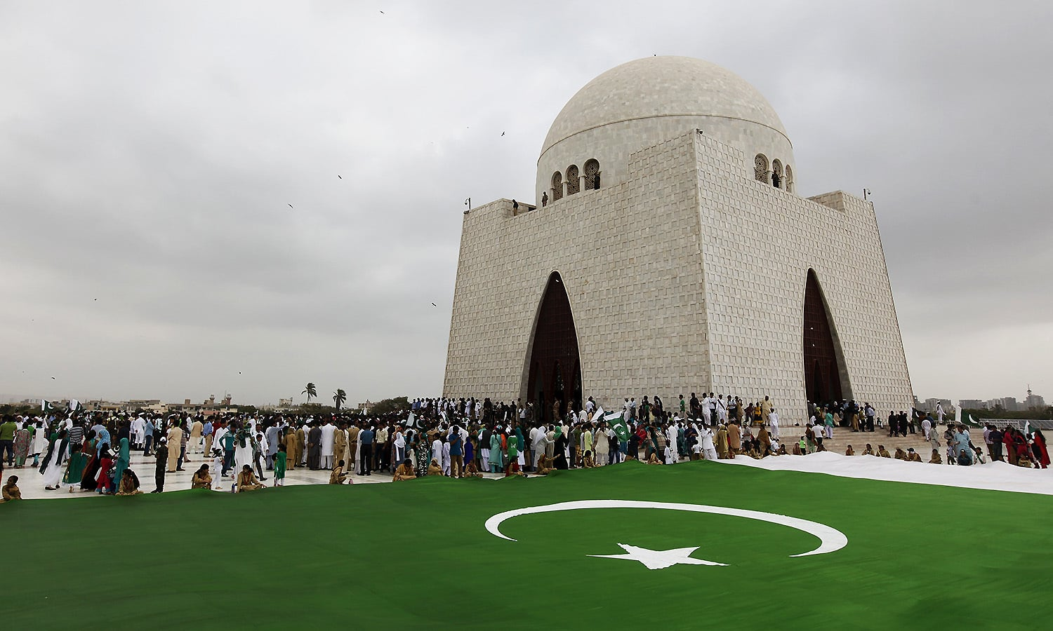 People gather near a national flag during a ceremony to celebrate the country's 69th Independence Day at the mausoleum of Muhammad Ali Jinnah in Karachi, Pakistan, August 14, 2015.  — Reuters