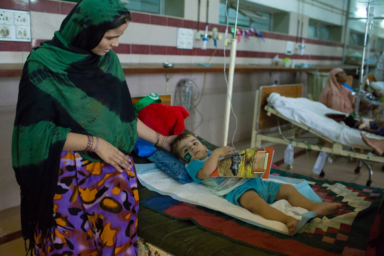 A mother tends to her son who is suffering from Gastroenteritis.