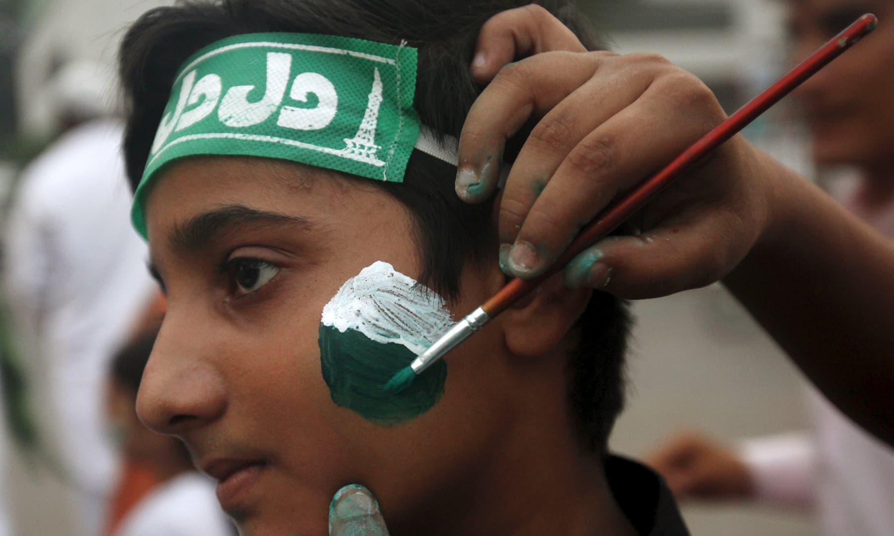 عوام نے 14 اگست کو منانے کے لیے طرح طرح کی تیاریاں کی اور چہرے پر ہرے سفید رنگوں سے پاکستانی پرچم بنایا — فوٹو رائٹرز